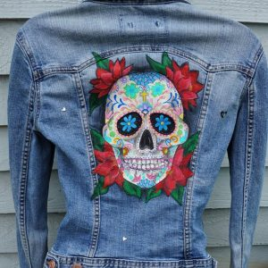denim jacket with a sugar skull painted on it. the skull covers most of the middle back section of the jacket and has four red floral arrancements behind it in the corners, if it was rectangular.