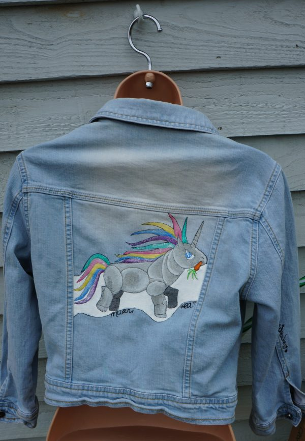 denim jacket with a cartoon image of a robot unicorn on it with a pastel rainbow tail and mane