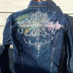 rear view of a denim jacket. The shoulders and part of the back are painted with a colour wash and on top of that is a mandala/henna style design that looks as though it is hangin from the shoulders.