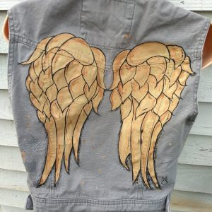 sleeveless khakhi coloured gilet. On the back it has hand painted wings like the ones on Daryl's jacket on the series The Walking Dead