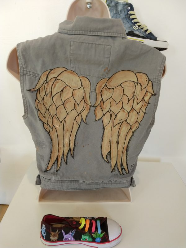 sleeveless khakhi coloured gilet. On the back it has hand painted wings like the ones on Daryl's jacket on the series The Walking Dead. The jacket is on a mannequin and below it is a picture of a sneaker with pokemon painted onto it.