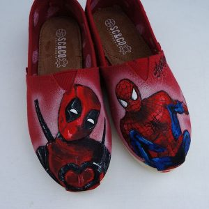 pair or red toms with deadpool and spiderman painted on them in realisitc style