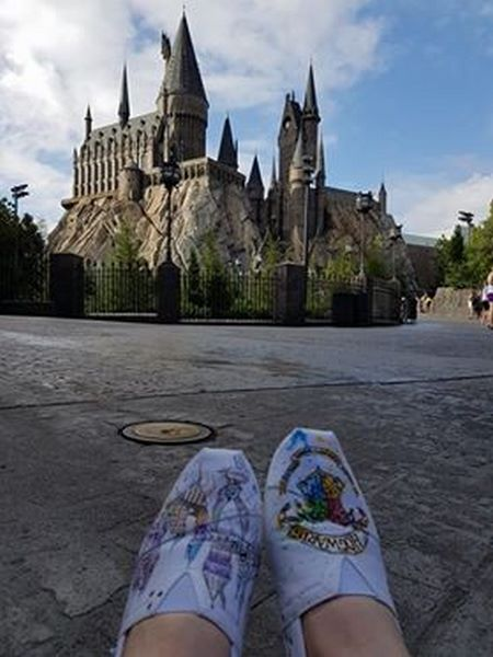 pair of white harry potter themed toms featuring picture of the castle. they are being worn by a person and in the background is the actual hogwarts castle