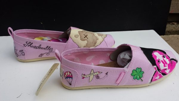 a side view of some pink toms with a travel themed design