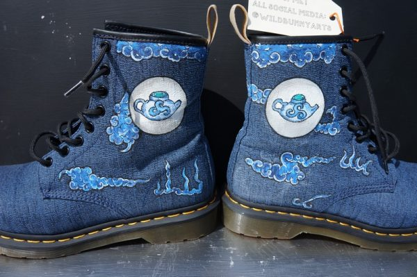 a pair of navy blue dr Martens with a chinese treapot design and chinese clouds