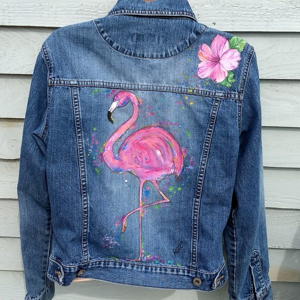 the back of a denim jacket with the picture of a famingo on it surrounded by paint splats. on the right hand shoulder is a hibiscus flower.