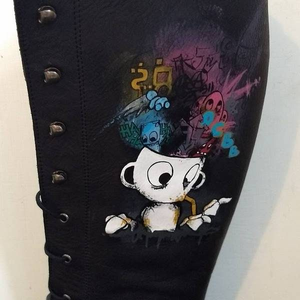 side of a leather calf boot with a cup headed cartoon character with pastel colured shapes coming out of their head