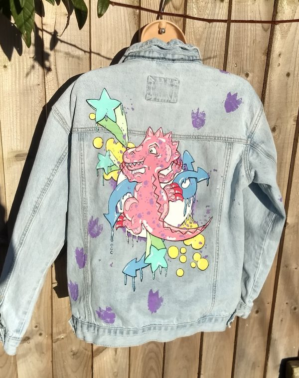 denim jacket with a cute picture of a pink dinosaur climbing up it. There are purple dinosaur prints travelling up from the left hip to the right shoulder. Pictured behind the dinosaur are various graffiti style stars, arrows and bubbles. The theme colour is pastel