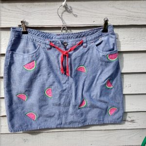 picture of a denim skirt with a red tie at the waist. It has small melon slices painted onto it in a random placement.