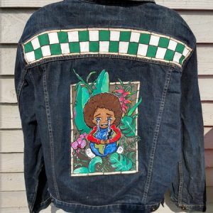 photo of the back of a denim jacket with a green and white checkerboard design across the shoulders and a picture of a bow ithe big brown hair sitting down holding a broke earht, His tears are flowing into the sea. Behind him are tropical leaves and flowers.