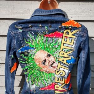 a denim jacket with the image of keith flint on it in bright colours and the word firestarter painted in yellow, vertically