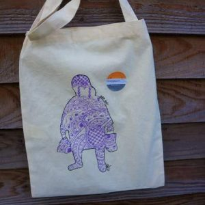 picture of a cream coloured cotton bag with an outline of an elderly lady filled in with purple henna tyle pattern
