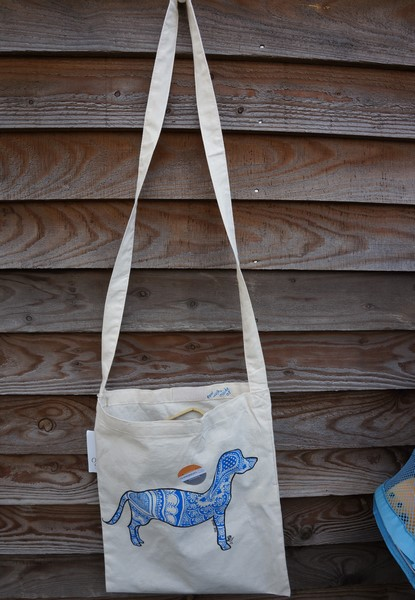 picture of a cotton tote bag with a long strap and an outline of a dog on it